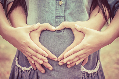 Couple making heart shape with hands over pregnant belly