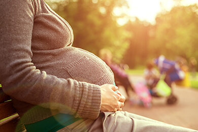 Pregnant woman sitting on a park bench